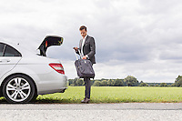 Full length of young businessman unloading suitcase from broken down car at countryside