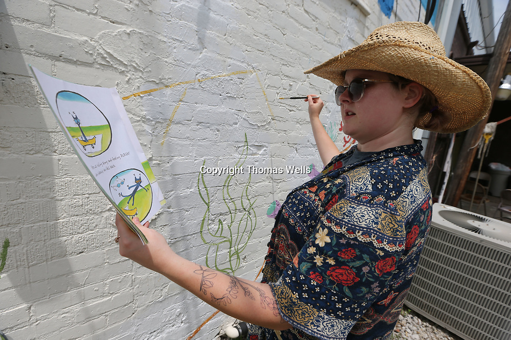 "Mckinnon Herring keeps the book ""Pete the Cat"" for a reference as she continues work on a mural on the TRC Tutoring and Consulting building in Saltillo."