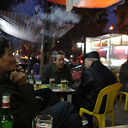 Locals drink beer in a bar on a street corner in the old quarter of Hanoi, Vietnam. 17th March 2012. Photo Tim Clayton
