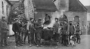 World War I 1914-1918:  German soldiers  round a mobile field kitchen in a French village.