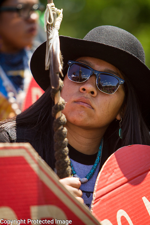"Carrie Sage Curley, San Carlos Apache, watches Wendsler Nosie, Sr, tribal councilman, speak to fellow members of the San Carlos Apache Tribe and their supporters in front of the United States Capitol to protest the transfer of Apache land to a private Australian-British mining corporation.  In December 2014, a rider to the National Defense Authorization Act handed over Oak Flat to a foreign-owned company looking to mine copper.  The Apache are currently ""occupying"" Oak Flat, and travelled to D.C. to protest the action.  In response, Rep. Raul Grijalva (D-AZ-3), proposed the Save Oak Flat Act (H.R. 2811) in June, 2015 to repeal the land exchange.  John Boal Photography"