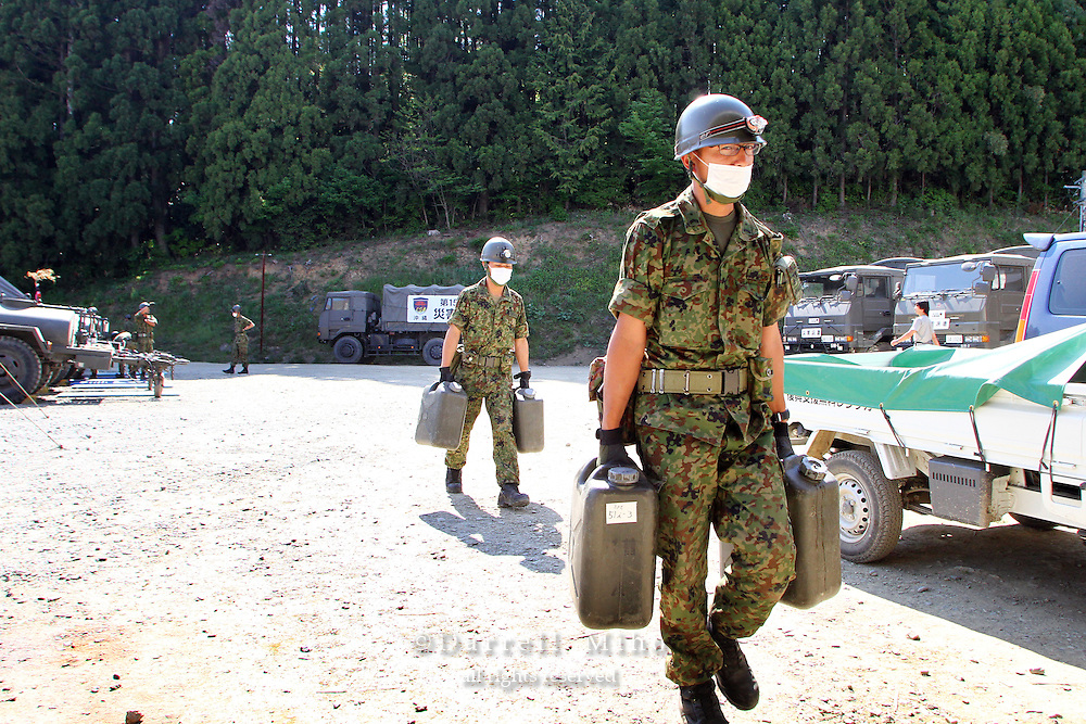 May 18, 2011; Minamisanriku, Miyagi Pref., Japan - A soldier from Japan's Self-Defense Forces carries in hot water for bathing at the Shizukawa High School Evacuation Center in Minamisanriku after the magnitude 9.0 Great East Japan Earthquake and Tsunami that devastated the Tohoku region of Japan on March 11, 2011.