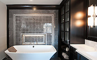A renovated home in South Oak Bay, Victoria, BC blends traditional architecture with contemporary style. The bathroom features elegant tile work and custom cabinetry.