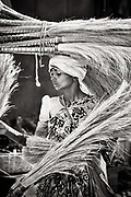 Woman loading brooms on het shoulders and head. Goa, India