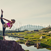 dramatic yoga pose on boulder in lake with reflection in mountains backlit morning sun