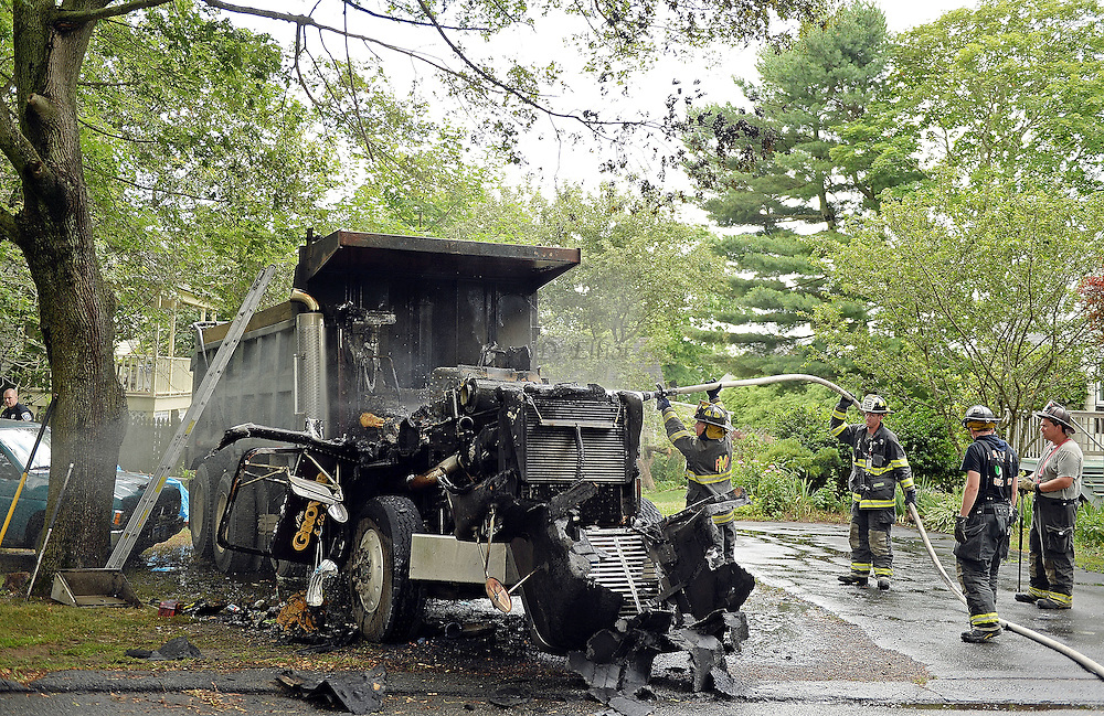 7/5/16 :: NEWS :: STAND ALONE :: Mystic firefighters hose down the engine block after extinguishing a fire that consumed the cab of the truck Tuesday, July 5, 2016 parked on Irving St. behind 40 West Mystic Ave. . (Sean D. Elliot/The Day)
