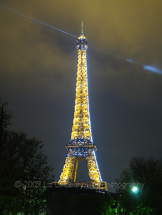 Eiffel Tower at night with rotating searchlight