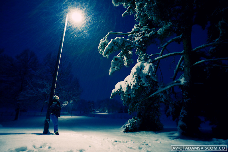 A woman stands under a light pole during a snow storm in Denver, CO.