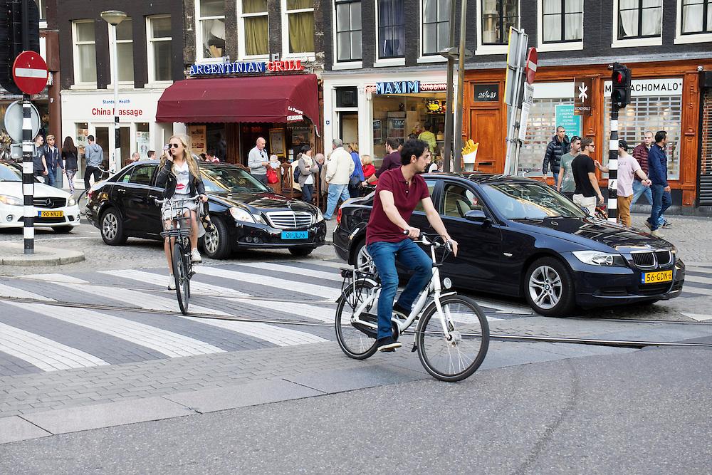 In Amsterdam komen afslaande auto's in conflict met fietsers. Een meisje zit al bellend op de fiets.<br /> <br /> In Amsterdam cars turning conflict with cyclists. A girl is phoning while riding on the bike.