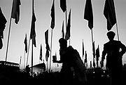 Silhouette of many flags and two individuals walking past. Glastonbury 2009