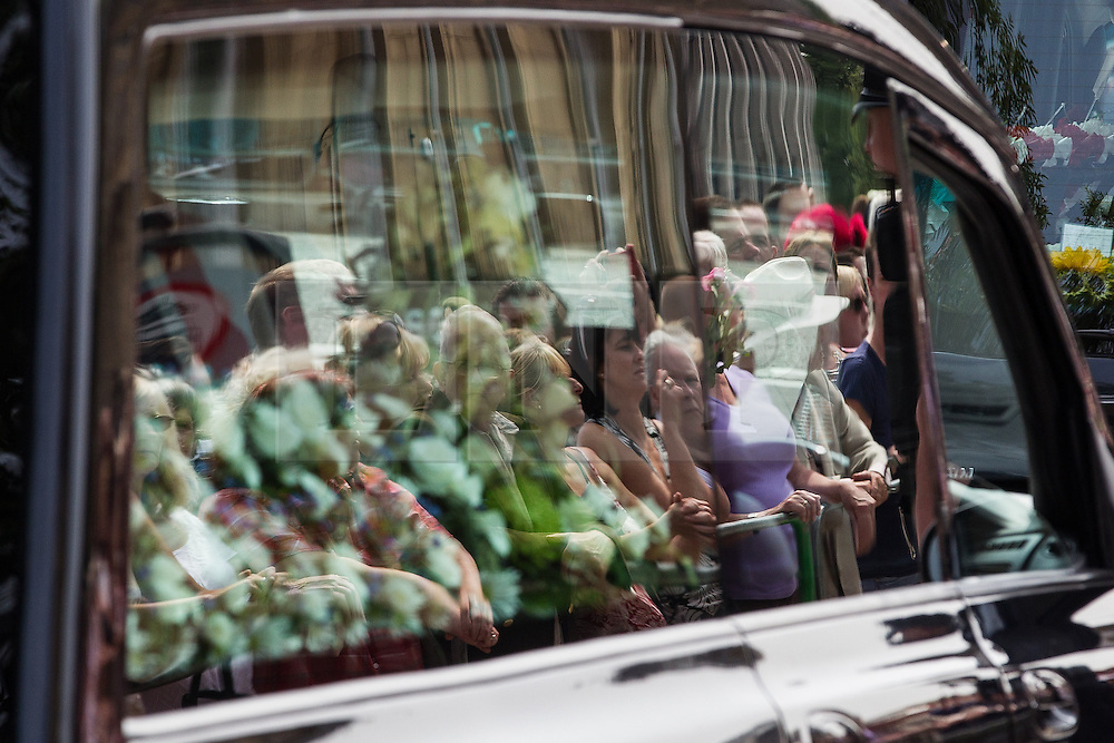© Licensed to London News Pictures . 12/07/2013 . Bury , UK . Onlookers reflected in the windows of the hearse with Lee Rigby 's coffin after the service . The funeral for Fusilier Lee Rigby at Bury Parish Church in Bury town centre today (Friday 12th July 2013) , watched by 100s of people . Fusilier Rigby's coffin was held in Bury Parish Church overnight , watched over by an honour guard of soldiers from the 2nd Battalion Royal Regiment of Fusiliers ( 2RRF ) . Rigby was brutally murdered in Woolwich , London on 22nd May 2013 . Photo credit : Joel Goodman/LNP