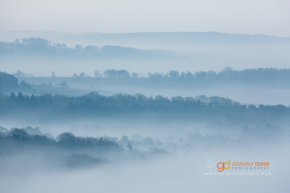 March mist! Atmospheric tree-lined layers looking down the Derwent Valley from Carl Wark, towards Froggatt and Curbar. Dawn. Derbyshire, Peak District, England, UK.