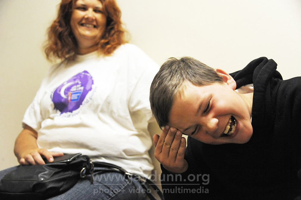 Nathaniel Ashlin, 11, has a laugh with his mom Joan Sassman as they wait for a shower at the Chinatown Health Services Center in Salinas. Nathaniel took the day off from school to be with his mom, who wasn't feeling well.
