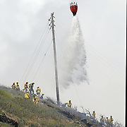 HFD Air One, makes an aerial water drop as HFD firefighters battle to contain a Hawaii Kai, Oahu brushfire before it crosses over the ridge from Pepeekeo St. to Kawaihae Dr and the condos below.  Photo by Barry Markowitz, 9/4/13, 11:45am