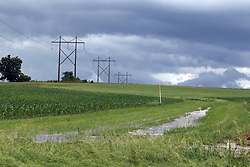 Water stands in a waterway between a pair of cornfields as the storm exits on the horizon behind some high voltage power distribution lines