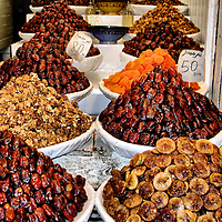 Candied Figs and Dates For Sale in Fes el Bali at Fez, Morocco<br /> Two thousand years ago, Nomads called Berbers began harvesting figs and dates in Morocco in northwestern Africa. When the Arabs conquered them in the seventh century, they brought along spices like ginger, cinnamon and caraway. Together the two cultures created the type of candied figs, dates, bananas, apricots and walnuts sold at Fez el Bali.