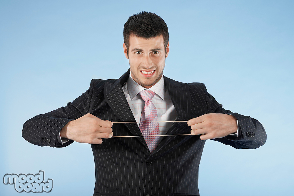 Businessman stretching rubber band on blue background portrait