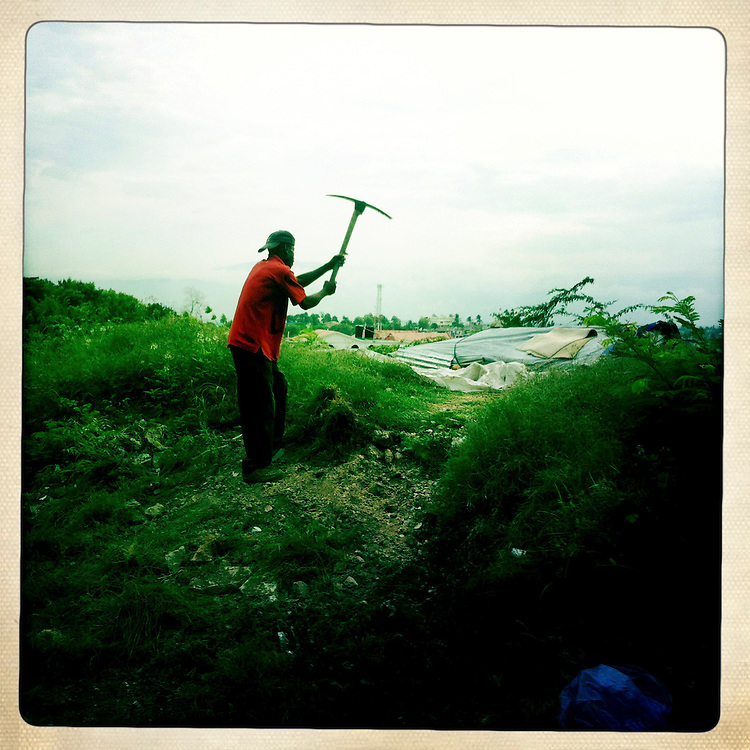 A man works with a pickaxe on Thursday, April 5, 2012 in Port-au-Prince, Haiti.