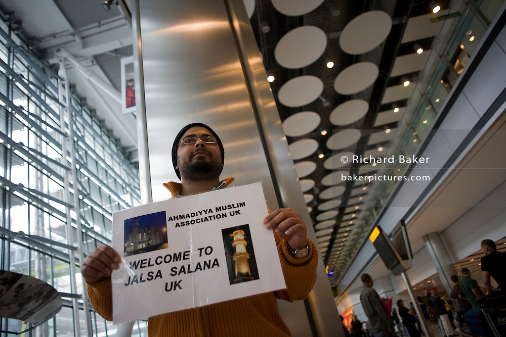 An Ahmadiyya mosque official holds a name card and awaits a fellow-Muslim in Arrivals at Heathrow airport's Terminal 5.