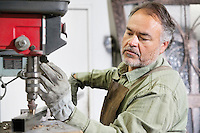 Mature metalworker working with machinery in workshop