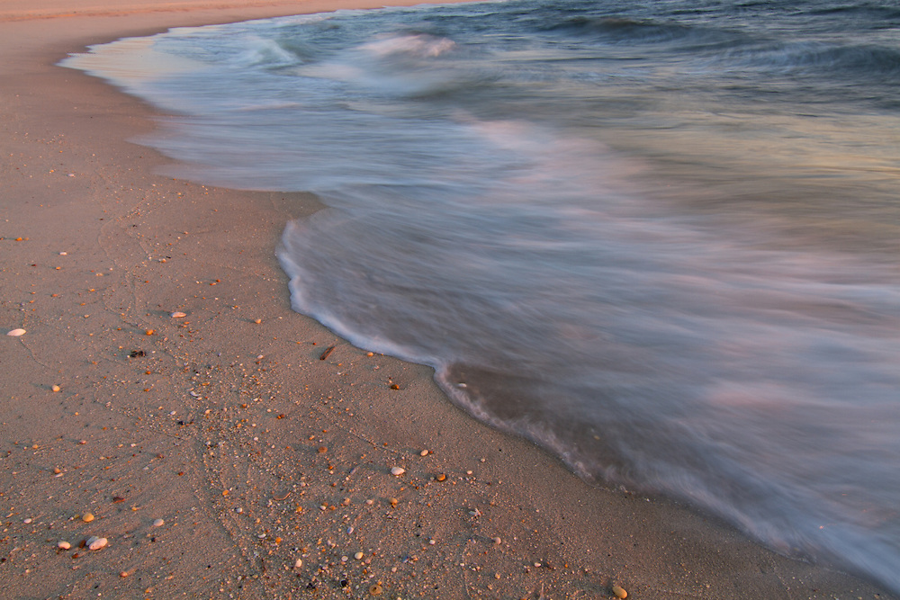 Waves wash over the beach at sunrise on Sandy Hook, Gateway National Recreation Area, NJ.