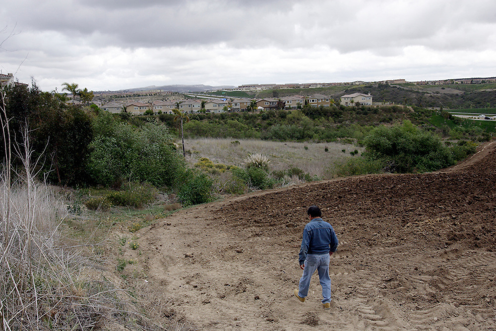 SAN DIEGO, CA, MAY 4, 2007:  Migrants who work the nearby fields or wait for work at day labor sites often use McGonigle Canyon in San Diego county as home. They construct living quarters out of branches, leaves and mud in the middle of a canyon lined with modern homes. Local activist Robert Baca, who runs a mobile health clinic for the migrants, descends into the canyon to check on migrants. (Photo by Todd Bigelow/Aurora) Please contact Todd Bigelow directly with your licensing requests.