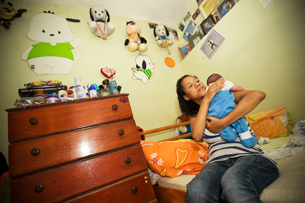 15-year-old mother, Yanaifre Acevedo, burps her newborn baby, Dilan, in a slum in Caracas, Venezuela. Acevedo, who wants to be a professional dancer, said she got pregnant by accident, but that she has a secret plan to have her aunt watch her baby so that she can go back to school. She also plans to get a job so that she and her boyfriend can move into their own apartment together. She says her boyfriend is excited to be a father, but he has hardly visited her and their son.