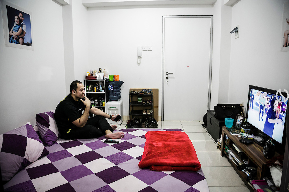 JAKARTA; TUESDAY, NOVEMBER 11, 2014; INDONESIA ECONOMIC RISING: Amir Wibowo, 29, a personal trainer, watches a TV show at his apartment during break time in Greenbay Pluit, North of Jakarta, Indonesia, on Tuesday, November 11, 2014. According to Asian Development Bank's 2014 report, Indonesia economy growth potential is in creative industry after for years relies heavily on natural resources such as mineral mining and palm oil. By the presidency of Joko Widodo, as a product of the third people election after the People Power Revolution in 1998, Indonesia is more confident in the economy growth and optimistic to become equal in quality to Brazil and China's economy growth. The emerging of Indonesia economy for the last one and a half decade after the end of Suharto's Dictatorship has been in significant way, the per capita growth has reached 400% under Susilo Bambang Yudhoyono presidency. Indonesia is home for 74 million of middle class as estimated by Boston Consulting Group, and  will double in 2020.