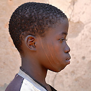 Benin, Natitingou November 26, 2006 - A young Boy shows his facial scars which represent the Prince of Djougou, a small city in the center of Benin. Scarification is used as a form of initiation into adulthood, beauty and a sign of a village, tribe, and clan.