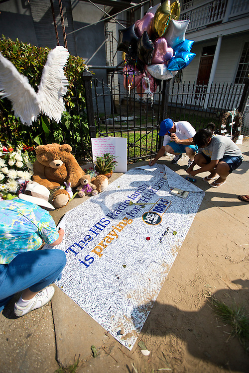 People writing condolences on a banner outside of the Emanuel AME Church in Charleston, SC after the shooting death of 9 people.