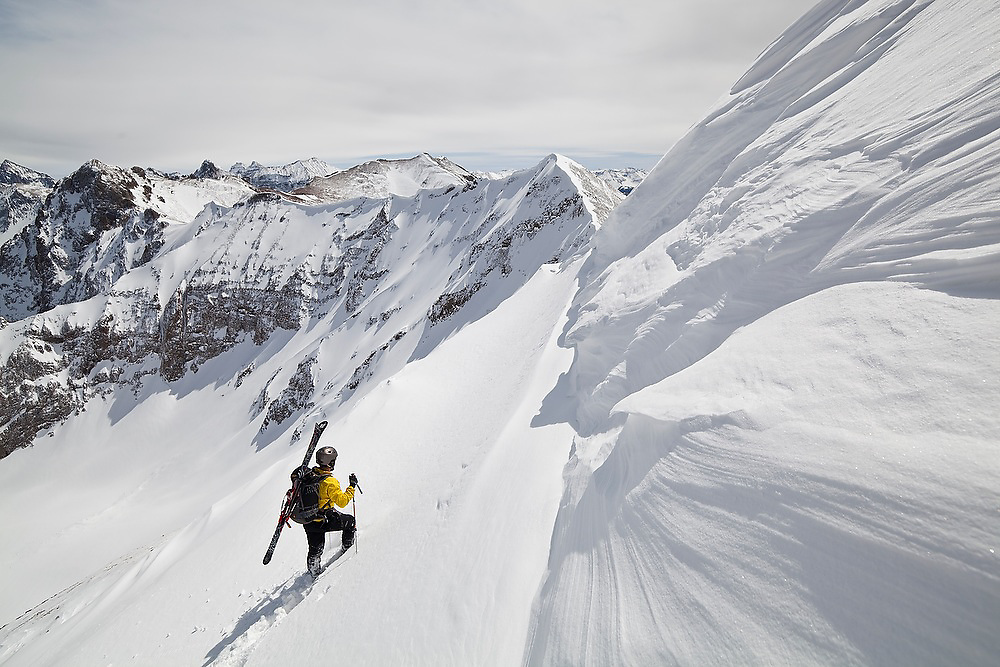 Backcountry skier Judd MacRae climbs to the summit of Hayden Peak, San Juan Mountains, Colorado. The Sneffels Range extends into the distance.