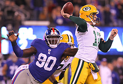 Dec 4, 2011; East Rutherford, NJ, USA; Green Bay Packers quarterback Aaron Rodgers (12) throws a pass while being pressured by New York Giants defensive end Jason Pierre-Paul (90) during the first half at MetLife Stadium.
