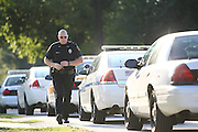 13 September 2010: A Springfield police officer walks back to his car in order to block off West State Street during a stand off between police and a subject in a house. The stand off started around 5 p.m. on Monday. Credit: David Welker/ Turfimages.com