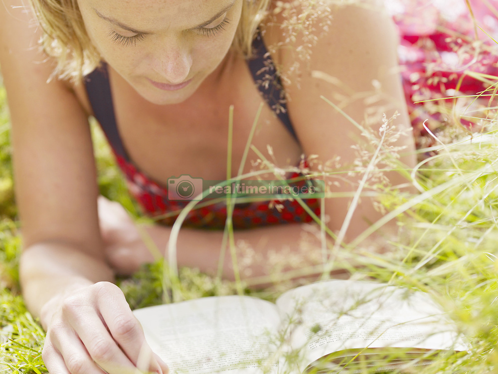 Aug. 23, 2007 - Woman lying in grass reading a book.. Model & Property Released (MR&PR) (Credit Image: © Cultura/ZUMAPRESS.com)