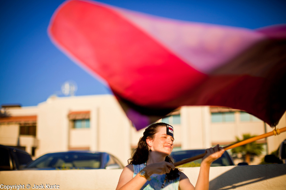 26 SEPTEMBER 2010 - PHOENIX, AZ: Susanna I. Astarte, from Mesa, AZ, a lesbian activist, waves gay rights flags during a picket of US Sen. John McCain in Phoenix, Sunday. About 200 people demonstrated and picketed against Arizona Republican Senator John McCain at the studios of KTVK TV in Phoenix, Sunday, Sept 26. They picketed the TV station because McCain was debating his opponents there. They were demonstrating against McCain's positions on the war in Afghanistan, Don't Ask Don't Tell (Gays in the military) and the DREAM Act (for immigrant rights). PHOTO BY JACK KURTZ