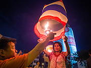 "17 NOVEMBER 2013 - BANGKOK, THAILAND:  People luanch  Yi Peng lanterns on Loy Krathong near Wat Yannawa in Bangkok. The Yi Peng lanterns are Loy Krathong tradition in Chiang Mai but they are becoming more popular  in Bangkok and central Thailand. Loy Krathong (also written as Loi Krathong) is celebrated annually throughout Thailand and certain parts of Laos and Burma (in Shan State). The name could be translated ""Floating Crown"" or ""Floating Decoration"" and comes from the tradition of making buoyant decorations which are then floated on a river. Loi Krathong takes place on the evening of the full moon of the 12th month in the traditional and they do this all evening on the 12th month Thai lunar calendar. In the western calendar this usually falls in November. The candle venerates the Buddha with light, while the krathong's floating symbolizes letting go of all one's hatred, anger, and defilements      PHOTO BY JACK KURTZ"