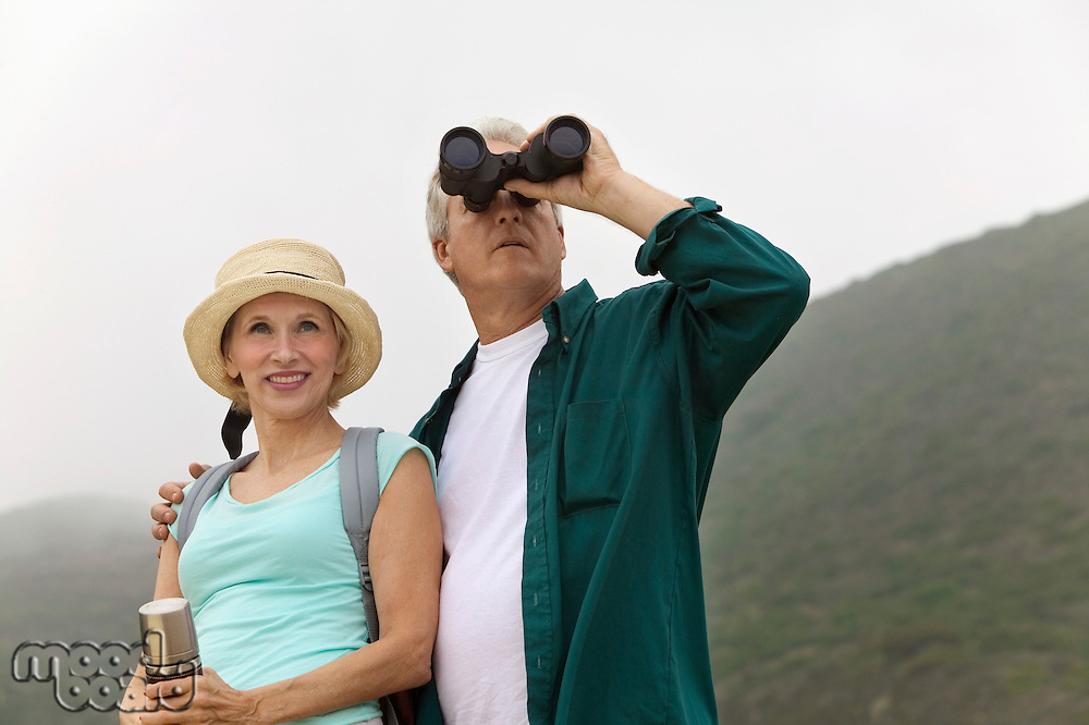 Middle-Aged Couple Looking Through Binoculars