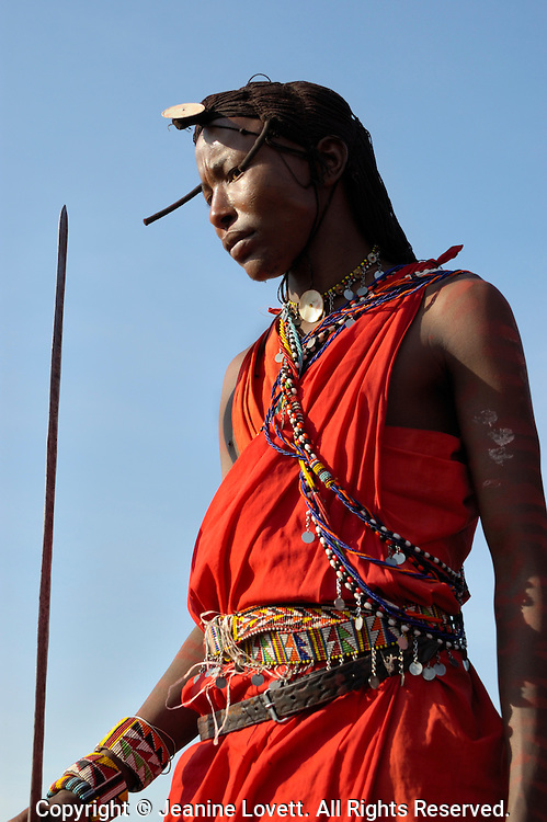 Masai warrior holding spear and wearing traditional wig.