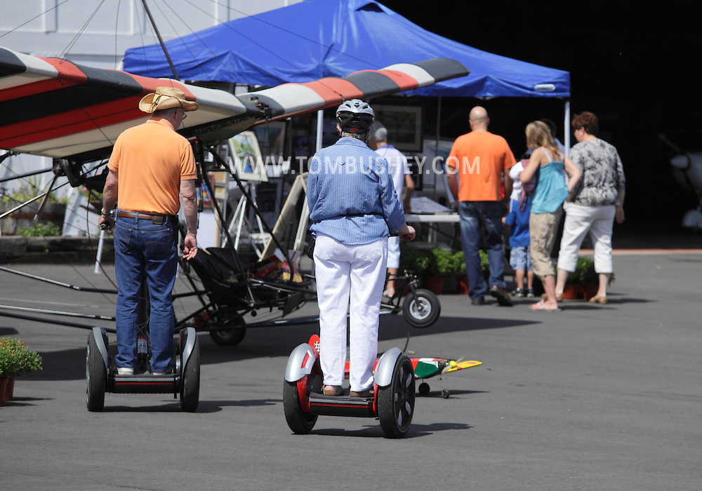 Wurtsboro, NY - An elderly couple riding on Segway Personal Transporters look at aircraft on display at Wurtsboro Airport on Aug. 30, 2009.