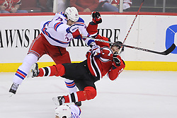 Jan 31; Newark, NJ, USA; New York Rangers center Brian Boyle (22) hits New Jersey Devils defenseman Adam Larsson (5) during the third period at the Prudential Center.  The Devils defeated the Rangers 4-3 in an OT shootout.