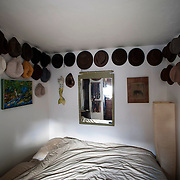 May 10, 2012 - Brooklyn, NY : The bedroom in musician and composer Michael Arenella's apartment on Douglas Street in Brooklyn is adorned with a collection of hats and ties, as well as paintings by his father, Joe Arenella. CREDIT : Karsten Moran for The New York Times