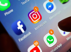 EMBARGOED TO 0001 MONDAY APRIL 15 Undated file photo of social media icons displayed on a mobile phone screen. One in four young people admits to struggling to respond to calls, texts and social media notifications, a survey has found.