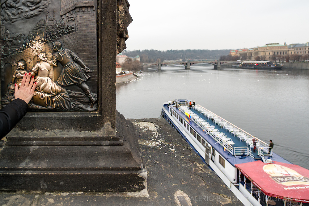 A hand touches a statue in Charles Bridge, wishing for good luck, below on a boat along Vltava River tourists take selfies.