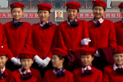 The portrait of Mao Zedong is seen as stewardesses pose for photos on Tiananmen Square before the opening session of the National Peoples Congress (NPC) outside the Great Hall of the People in Beijing, China, on 05 March 2011. The NPC has over 3,000 delegates and is the world's largest parliament or legislative assembly though its function is largely as a formal seal of approval for the policies fixed by the leaders of the Chinese Communist Party.
