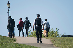 © Licensed to London News Pictures. 14/04/2020. London, UK. A police officer patrolling Primrose Hill in North London, during a pandemic outbreak of the Coronavirus COVID-19 disease. The public have been told they can only leave their homes when absolutely essential, in an attempt to fight the spread of coronavirus COVID-19 disease. Photo credit: Ben Cawthra/LNP