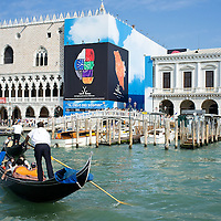 VENICE, ITALY - JULY 29:  A gondola sails in St Marks Basin in front of Palazzo Ducale half covered by a sponsor on July 29, 2011 in Venice, Italy. The over 400 year old Rialto Bridge is one of Italy's s most famous sights. Millions of tourists walk over it every year creating a heavy toll on the structure of the bridge. The Rialto will be restored soon through the financial backing of a sponsor.