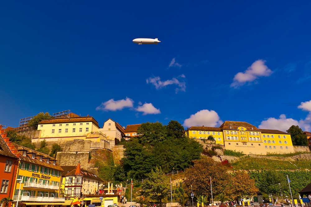 A zeppelin flies above the medieval city of Meersburg on Lake Constance (Bodensee), with vineyards below, Baden-Württemberg, Germany
