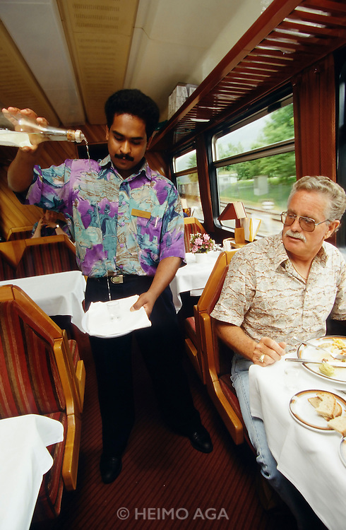 A Sri Lankan waiter of the Glacier Express demonstrates his skills at Schnaps pouring.