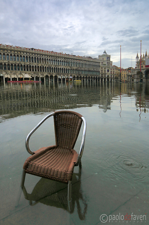 """A chair presumably belonging to Café Florian in Piazza San Marco floating in about 30 cms (1 foot) of water. Taken on an early morning at the end of January when the rising tide had already completely flooded the city, producing that phenomenon known as """"acqua alta""""."""