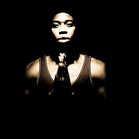 Portrait of young African American man praying with black backdrop